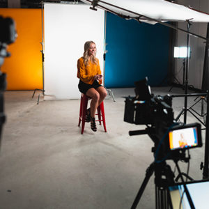 A girl sitting on a video production set and being filmed for an interview