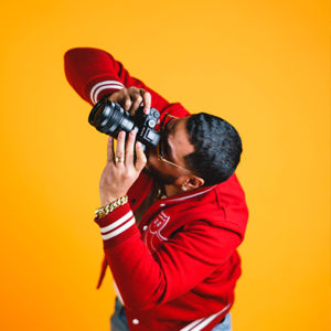 Man in a red jacket and glasses holding a Sony A7rii camera and pointing it upward