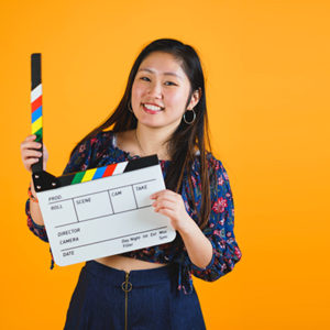 Girl holding a a video production clapper board against a yellow background and smiling